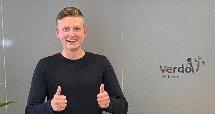 Gertjan Punt voor glazen ruit met logo Verdo Werkt. Hij steekt twee duimen omhoog